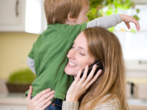 Mother on the phone holding a child